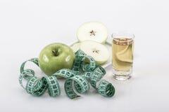 Φρούτα και χυμός της Apple που περιβάλλονται με την πράσινη ταινία μέτρησης Στοκ Φωτογραφία