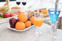 Φρούτα και χυμός φρούτων στο μαρμάρινο μετρητή στο δωμάτιο κουζινών Apple α Στοκ εικόνα με δικαίωμα ελεύθερης χρήσης