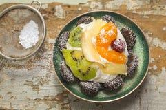 Φρούτα ξινά με το ακτινίδιο και aple στο πράσινο πιάτο στον παλαιό πίνακα Στοκ Φωτογραφίες