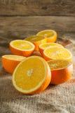 Φρούτα πορτοκαλιών και πορτοκαλιά φέτα στον ξύλινο πίνακα και το αναδρομικό ύφασμα στοκ εικόνες με δικαίωμα ελεύθερης χρήσης