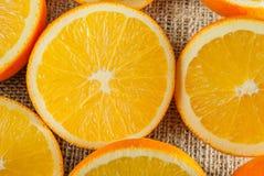Φρούτα πορτοκαλιών και πορτοκαλιά φέτα στον ξύλινο πίνακα και το αναδρομικό ύφασμα στοκ φωτογραφίες