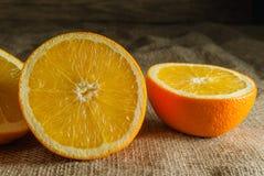 Φρούτα πορτοκαλιών και πορτοκαλιά φέτα στον ξύλινο πίνακα και το αναδρομικό ύφασμα στοκ εικόνες