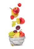 Φρούτα που εμπίπτουν σε ένα κύπελλο γυαλιού στο λευκό στοκ εικόνες