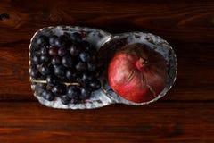 Φρούτα σε ένα πιάτο, τα σταφύλια και το ρόδι στοκ εικόνα