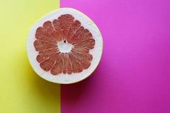 Φρούτα σταφυλιών μισά σε ένα ρόδινο και κίτρινο υπόβαθρο Στοκ φωτογραφία με δικαίωμα ελεύθερης χρήσης