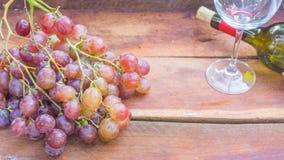 Φρούτα σταφυλιών και μπουκάλι κρασιού σε ξύλινο Στοκ Εικόνες