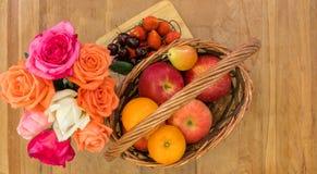 Φρούτα στο καλάθι με τα τριαντάφυλλα teak στον πίνακα Στοκ Φωτογραφίες
