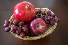 Φρούτα στο καλάθι με το ρόδι Στοκ Φωτογραφίες