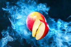 Φρούτα της Apple στο υπόβαθρο με τον καπνό από το ηλεκτρονικό τσιγάρο Στοκ Εικόνες