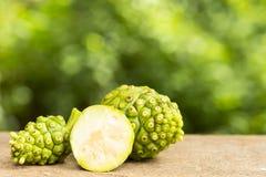 Φρούτα της Noni και φέτα noni στον ξύλινο πίνακα και το πράσινο υπόβαθρο Φρούτα για την υγεία και χορτάρι για την υγεία Στοκ Εικόνα