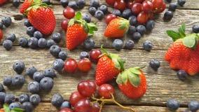 Φρούτα φραουλών σταφυλιών βακκινίων στο ξύλινο πιάτο στο ξύλινο βίντεο hd υποβάθρου ΣΕ ΑΡΓΗ ΚΊΝΗΣΗ απόθεμα βίντεο