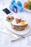 Φρυγανιά από ένα ψωμί σιταριού με το τυρί και τις ντομάτες και το αυγό Χορτοφάγα τρόφιμα σε ένα άσπρο πιάτο και μπλε αλτήρες και  Στοκ φωτογραφία με δικαίωμα ελεύθερης χρήσης