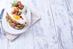 Φρυγανιά από ένα ψωμί σιταριού με το τυρί και τις ντομάτες και το αυγό Χορτοφάγα τρόφιμα σε ένα άσπρο πιάτο και ένα ξύλινο υπόβαθ Στοκ Εικόνα