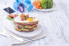 Φρυγανιά από ένα ψωμί σιταριού με το τυρί και τις ντομάτες και το αυγό Χορτοφάγα τρόφιμα σε ένα άσπρο πιάτο και μπλε αλτήρες και  Στοκ Εικόνες