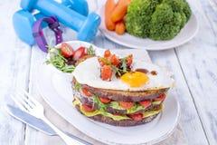 Φρυγανιά από ένα ψωμί σιταριού με το τυρί και τις ντομάτες και το αυγό Χορτοφάγα τρόφιμα σε ένα άσπρο πιάτο και μπλε αλτήρες και  Στοκ εικόνες με δικαίωμα ελεύθερης χρήσης