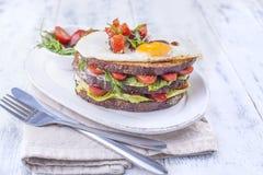 Φρυγανιά από ένα ψωμί σιταριού με το τυρί και τις ντομάτες και το αυγό Χορτοφάγα τρόφιμα σε ένα άσπρο πιάτο και μπλε αλτήρες για  Στοκ Εικόνες