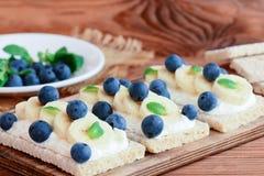 Φρυγανιά εγχώριων παξιμαδιών με το τυρί, την μπανάνα και τα μούρα εξοχικών σπιτιών στον ξύλινο πίνακα Υγιή σάντουιτς με τη φωτογρ Στοκ εικόνα με δικαίωμα ελεύθερης χρήσης
