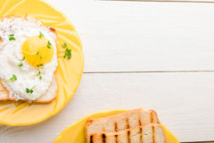 Φρυγανιά με το αυγό στο κίτρινο πιάτο με την μικροϋπολογιστής-πρασινάδα στο άσπρο ξύλινο υπόβαθρο Τοπ άποψη προγευμάτων Healty δι στοκ φωτογραφίες με δικαίωμα ελεύθερης χρήσης