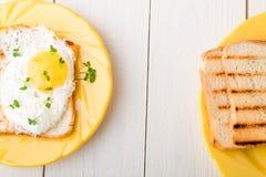 Φρυγανιά με το αυγό στο κίτρινο πιάτο με την μικροϋπολογιστής-πρασινάδα στο άσπρο ξύλινο υπόβαθρο Τοπ άποψη προγευμάτων Healty δι στοκ εικόνες με δικαίωμα ελεύθερης χρήσης