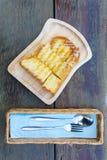 Φρυγανιά που ολοκληρώνεται με το συμπυκνωμένο γάλα σε ένα ξύλινο πιάτο με τα μαχαιροπήρουνα σε ένα κιβώτιο στον ξύλινο πίνακα Στοκ Εικόνες
