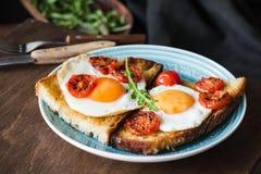Φρυγανιά προγευμάτων με το αυγό, το arugula και την ψημένη ντομάτα, άποψη κινηματογραφήσεων σε πρώτο πλάνο Στοκ εικόνα με δικαίωμα ελεύθερης χρήσης