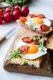 Φρυγανιά προγευμάτων με το αυγό, το arugula και την ψημένη ντομάτα, άποψη κινηματογραφήσεων σε πρώτο πλάνο Στοκ Φωτογραφία