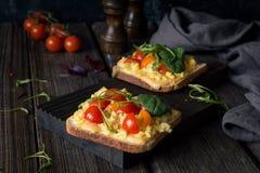 Φρυγανιά προγευμάτων: ψημένο ψωμί, ανακατωμένα αυγά, τυρί και ντομάτα Στοκ φωτογραφία με δικαίωμα ελεύθερης χρήσης