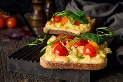 Φρυγανιά προγευμάτων: ψημένο ψωμί, ανακατωμένα αυγά, τυρί και ντομάτα Στοκ Εικόνες