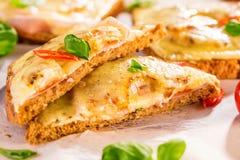 Φρυγανιά της Χαβάης με το ζαμπόν, το τυρί και τον ανανά σε έναν τέμνοντα πίνακα στοκ εικόνες