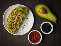Φρυγανιά ψωμιού μαγιάς και τεμαχισμένος πολτός αβοκάντο με το μαύρο πιπέρι σουσαμιού και τσίλι στοκ φωτογραφία