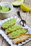 Φρυγανιές με το αβοκάντο guacamole στην άσπρη κινηματογράφηση σε πρώτο πλάνο πιάτων στον αγροτικό ξύλινο πίνακα Πρόγευμα διατροφή στοκ εικόνες