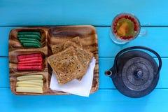 Φρυγανιές με τρία είδη τυριού στο ξύλινα πιάτο, teapot και το φλυτζάνι του τσαγιού στοκ φωτογραφία
