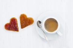 Φρυγανιές στη μορφή καρδιών με τη μαρμελάδα και το φλιτζάνι του καφέ φρούτων Στοκ Εικόνες