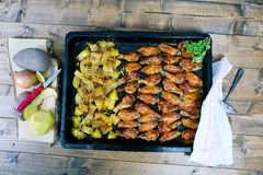 Φτερά κοτόπουλου με τις ψημένες πατάτες Στοκ Εικόνες