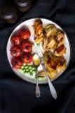 Φτερά κοτόπουλου, ψημένα ντομάτα κερασιών και πράσινα μπιζέλια στο άσπρο πιάτο, υγιές γεύμα γευμάτων Στοκ Φωτογραφία