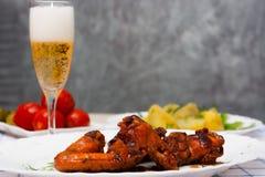 Φτερά κοτόπουλου που ψήνονται στη σχάρα με τις βρασμένες πατάτες και που μαρινάρονται tomatoe Στοκ εικόνα με δικαίωμα ελεύθερης χρήσης