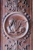 Φτερωτό λιοντάρι που χαράσσεται στην ξύλινη πύλη μιας αρχαίας εκκλησίας Στοκ Φωτογραφία