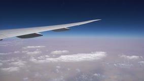 Φτερό αεροπλάνων πέρα από το μπλε ουρανό οριζόντων - υψηλό επάνω από τα σύννεφα, άποψη από το παράθυρο αεροπλάνων φιλμ μικρού μήκους