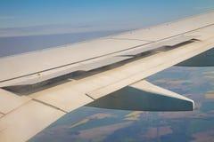 Φτερό αεροπλάνων με τη αεροτομή ανοικτή στον ουρανό πέρα από το έδαφος Στοκ Φωτογραφίες