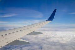 Φτερό αεροπλάνων στον ουρανό και πέρα από τη θάλασσα με τα σύννεφα Στοκ Εικόνα