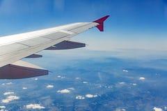 Φτερό αεροσκαφών στα σύννεφα, μύγες στο υπόβαθρο πόλεων στοκ εικόνα