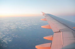 Φτερό ενός αεροπλάνου που πετά επάνω από τα σύννεφα ανατολής Στοκ Εικόνες