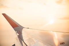 Φτερό του αεροπλάνου στον ουρανό σύννεφων από το παράθυρο το πρωί Στοκ Φωτογραφίες