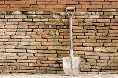 Φτυάρι στο τούβλινο υπόβαθρο τοίχων Στοκ Φωτογραφίες