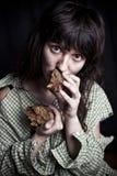 Φτωχή γυναίκα επαιτών με ένα κομμάτι του ψωμιού στοκ εικόνα