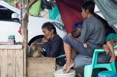 Φτωχή οικογένεια που ζει στις οδούς που πωλούν τα κεριά και το ιατρικό πετρέλαιο στοκ εικόνα