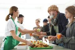 Φτωχοί άνθρωποι που λαμβάνουν τα τρόφιμα από τους εθελοντές στοκ φωτογραφίες