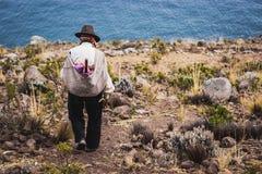 Φτωχός άνθρωπος που περπατά κάτω από έναν απότομο βράχο, νησί Taquile, λίμνη Titicaca, Περού στοκ εικόνα