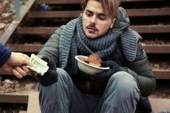Φτωχός νεαρός άνδρας που ικετεύει για τα χρήματα στα σκαλοπάτια υπαίθρια στοκ φωτογραφίες με δικαίωμα ελεύθερης χρήσης