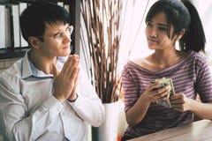 Φτωχός σύζυγος που ικετεύει τη σύζυγό του για τα χρήματα μετρητών στοκ εικόνα